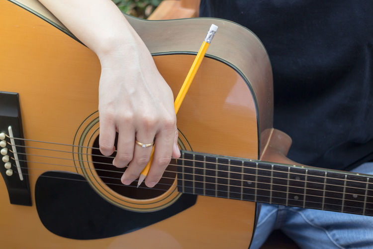 Midsection Of Men Holding Pencil While Playing Guitar