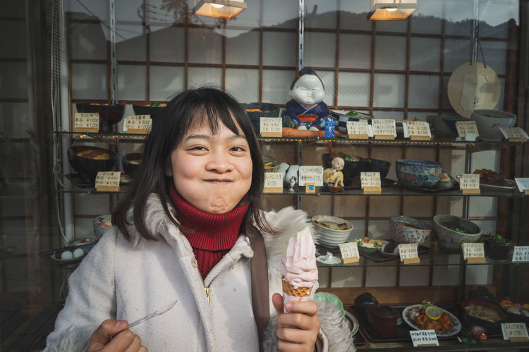 Portrait of woman making a face while holding ice cream in store