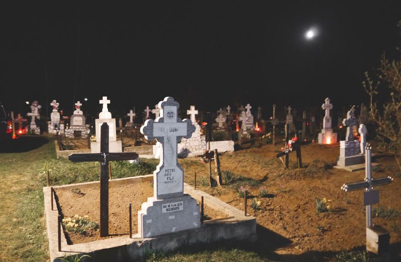 Illuminated cemetery against sky at night