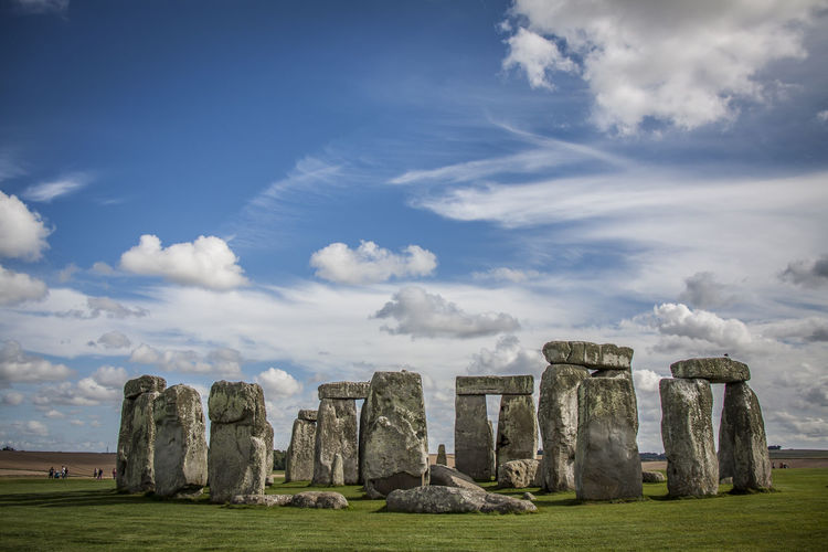 Stonehenge on field against cloudy sky