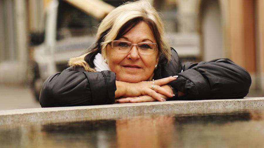 Portrait of senior woman with eyeglasses leaning on retaining wall