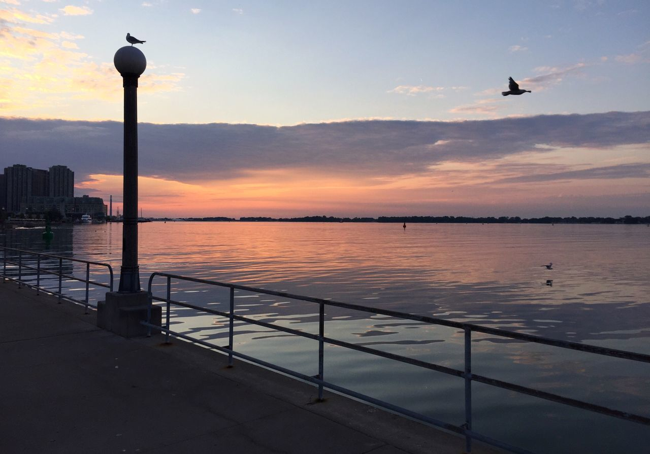 sunset, water, sea, sky, nature, beauty in nature, scenics, tranquil scene, silhouette, tranquility, outdoors, waterfront, cloud - sky, no people, built structure, horizon over water, architecture, beach, building exterior, flying, bird