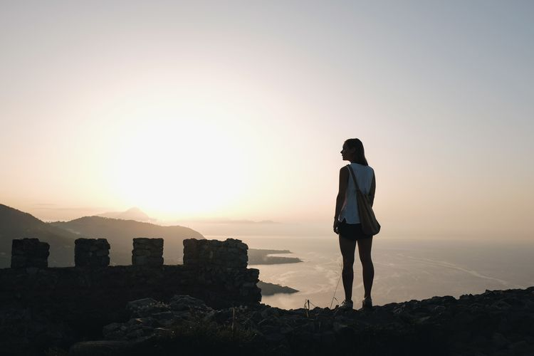 Rear View Of Young Woman Standing On Cliff Against Sea During Sunset