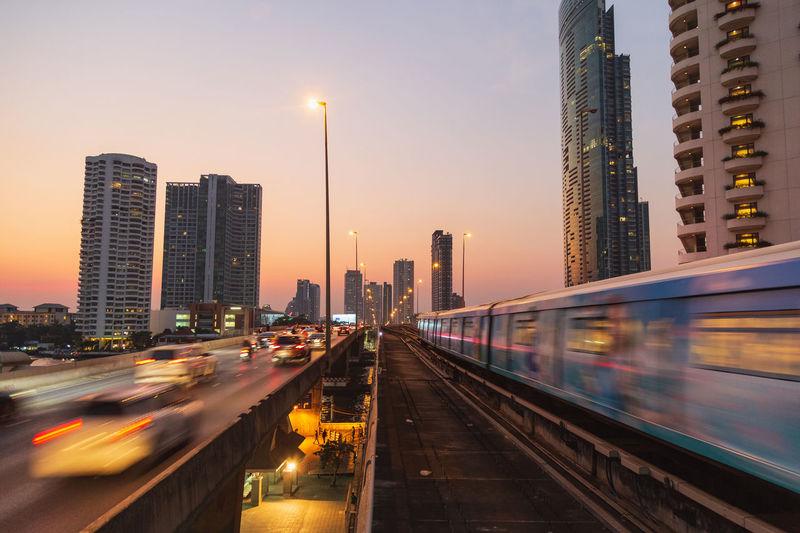 Illuminated city buildings against sky at dusk