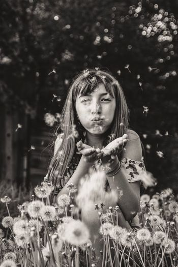 Portrait of girl holding plant on field
