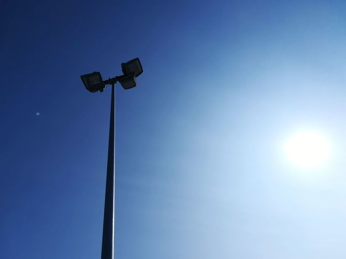 Low angle view of illuminated street light against clear blue sky