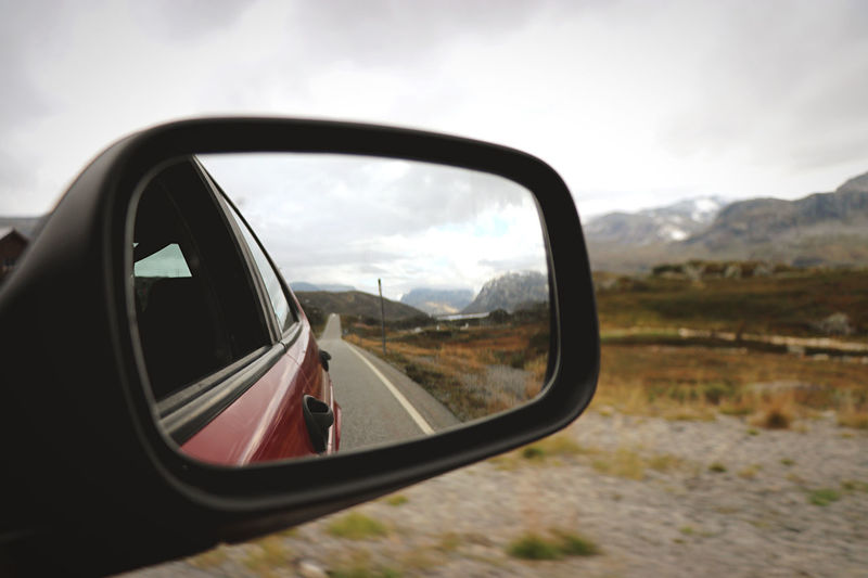 Road and landscape reflecting on side-view mirror of car against sky