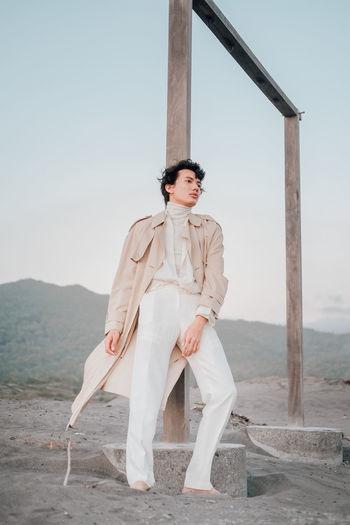 Full length portrait of woman standing on land against sky