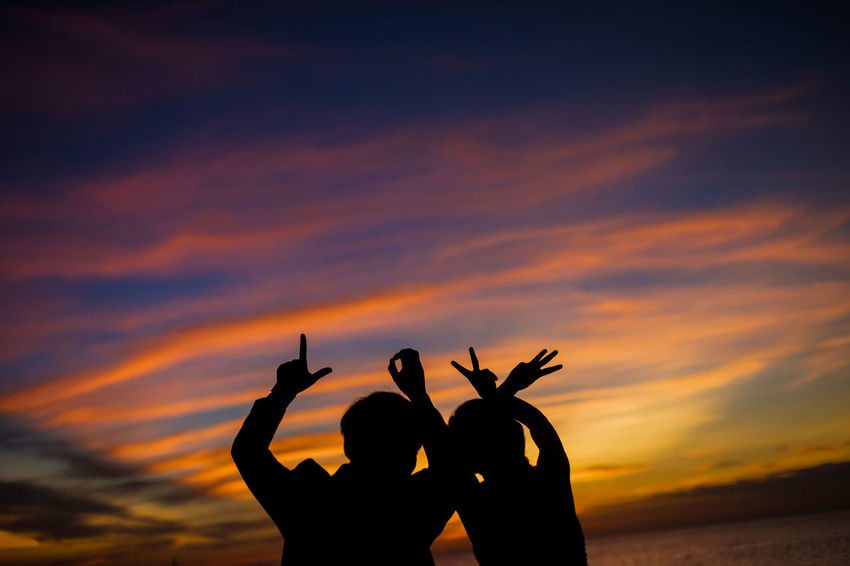 Beauty In Nature Cloud - Sky Gesturing Hand Sign Horn Sign Human Body Part Human Finger Human Hand Leisure Activity Lifestyles Men Nature Orange Color Outdoors Peace Sign - Gesture People Real People Sign Language Silhouette Sky Sunset Togetherness Women