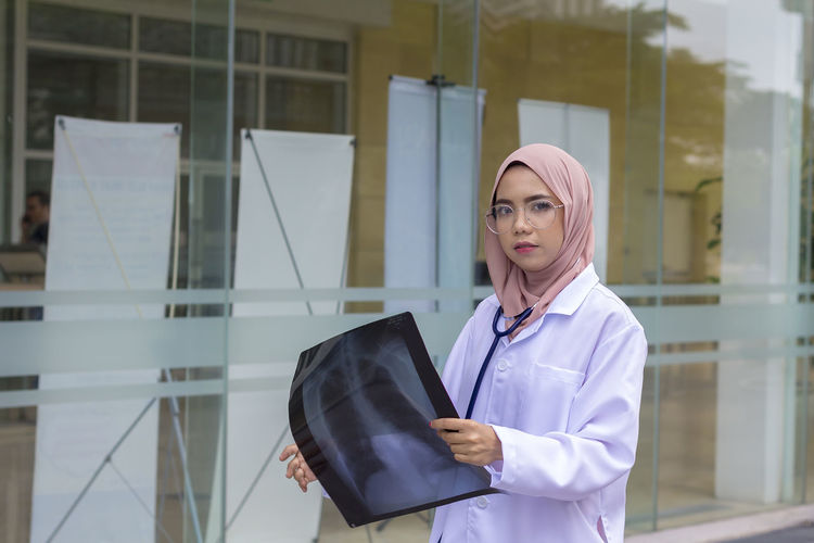 Portrait of female doctor holding x-ray while standing outside hospital