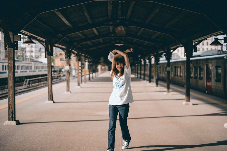 Full length portrait of woman standing at railroad station