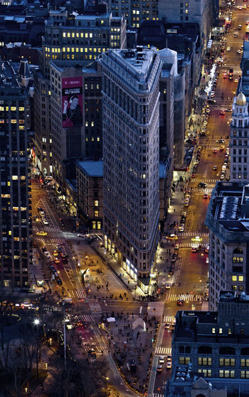 High angle view of road by flatiron building in city at dusk