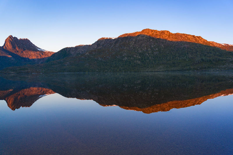 Beautiful mountain range landscape reflected on smooth water surface of lake Dove. Tasmania, Australia Nature Landscape Mountain Cradle Mountain Dove Lake Lake Water Reflection Sunrise Mirror Like Water Smooth Blue Sky Panoramic Australia Central Highlands Tasmania Beautiful National Park Outdoors Cradle Mountain National Park Day Wilderness