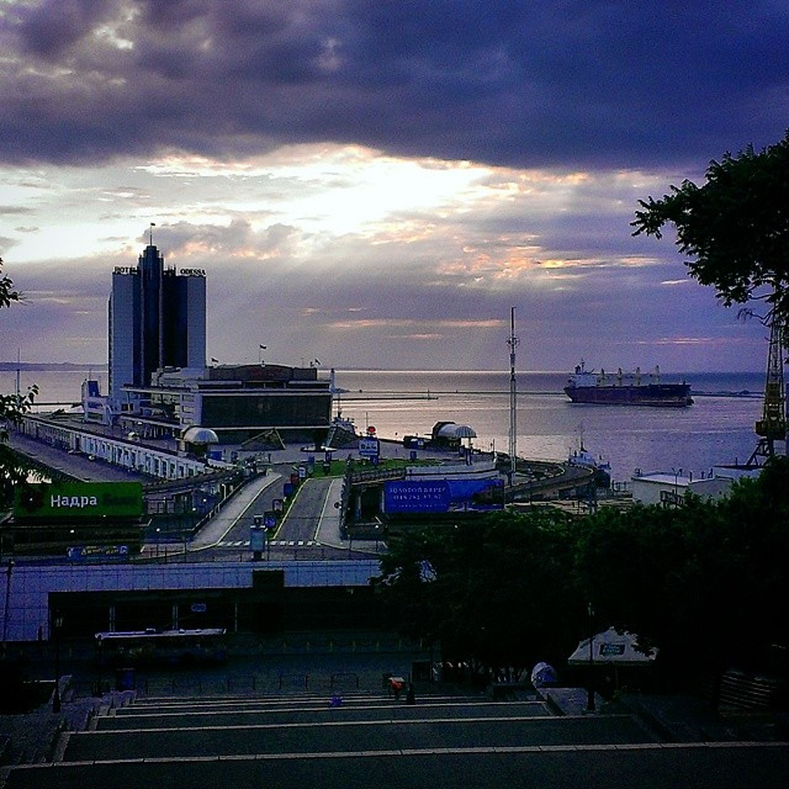sky, cloud - sky, water, sunset, transportation, nautical vessel, cloudy, mode of transport, sea, moored, cloud, built structure, harbor, city, building exterior, boat, architecture, tree, nature, high angle view