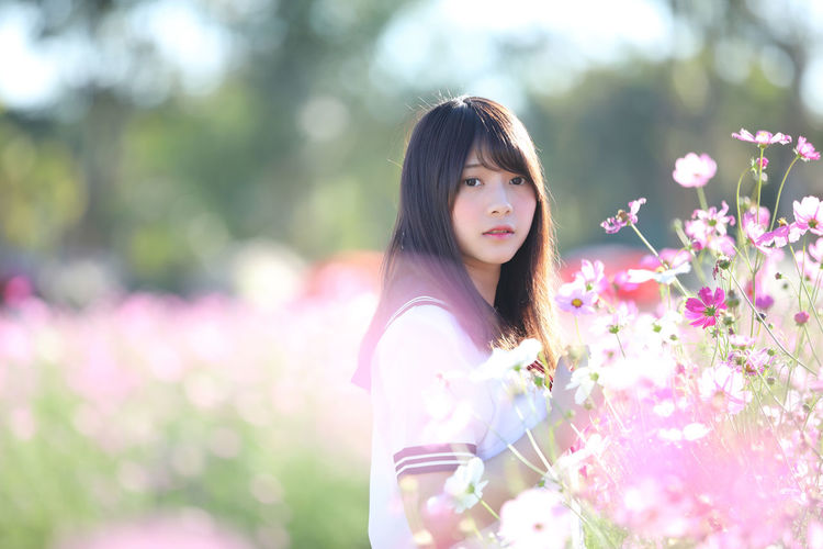 Side view portrait of beautiful young woman by flowering plants in park