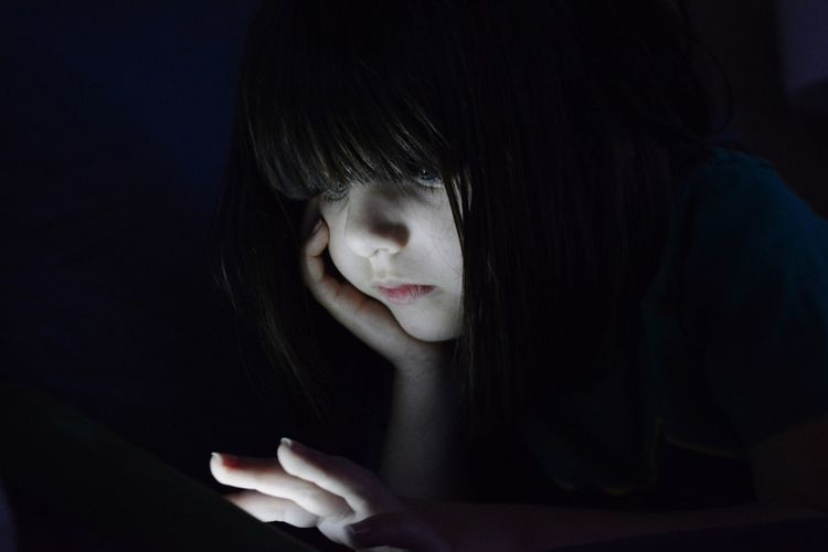 Close-Up Of Girl Using Technology In Darkroom
