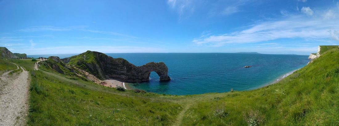 Durdle Door on the Jurassic Coast, UK Durdle Door, Dorset Beach Beauty In Nature Blue Cloud - Sky Day Grass Green Color Horizon Over Water Landscape Nature No People Outdoors Panoramic Panoramic Photography Scenics Sea Sky Tranquil Scene Tranquility Water