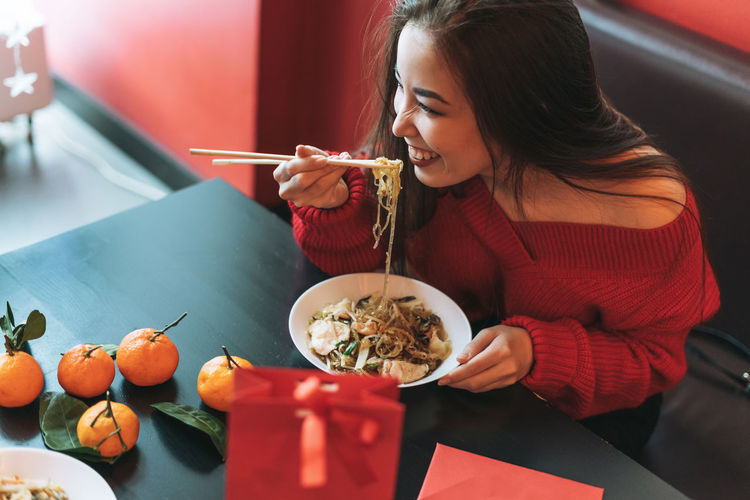 Beautiful asian woman in red clothes eating noodles with chopsticks in chinese vietnamese restaurant
