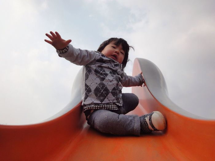 Low angle view of cute baby girl sitting on orange slide against sky