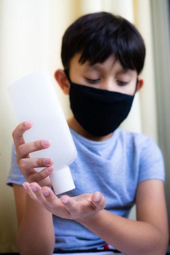 Boy taking sanitizer on hand