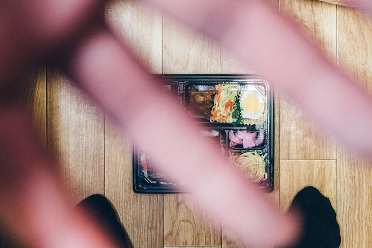 Close-Up Of Human Hand Against Food On Floor