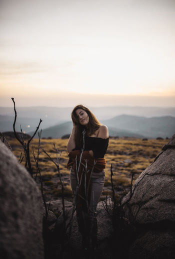 Woman posing on rock against sky during sunset