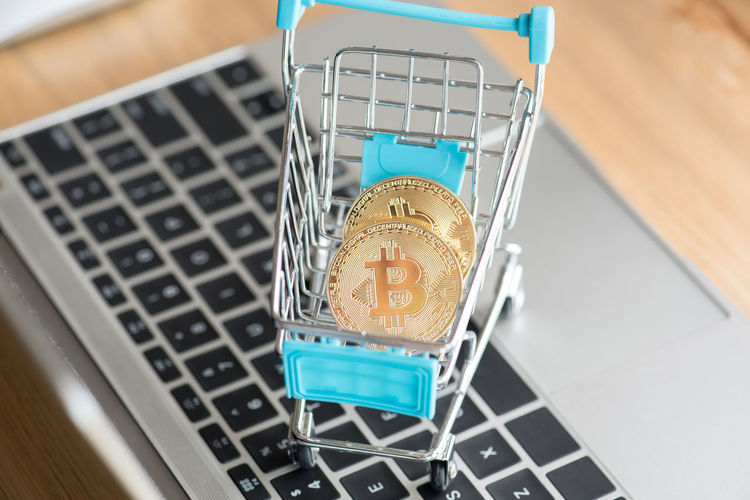 High angle view of bitcoins in shopping cart on laptop at table