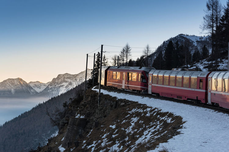 Train on snow covered mountains against sky