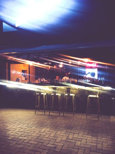 Shot on iPhone 5S Illumination Light Lights Bar High Chair Chairs Cafe At Night Cafe Blurred Smudged Illuminated Group Of People Night Real People Transportation Seat Mode Of Transportation Men Light - Natural Phenomenon Architecture Built Structure City