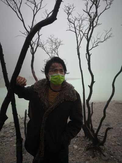 Portrait of man wearing surgical mask while standing against trees during winter