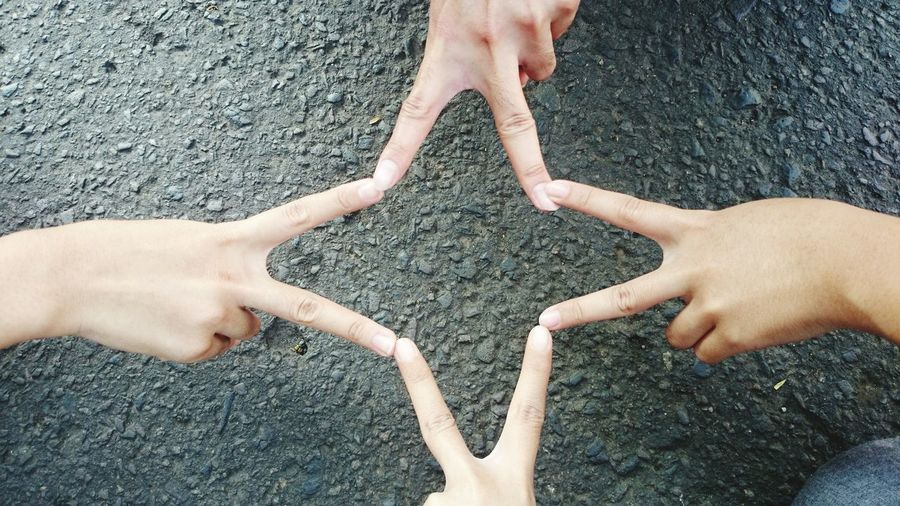 Directly Above Shot Of Cropped Friends Joining Fingers On Road