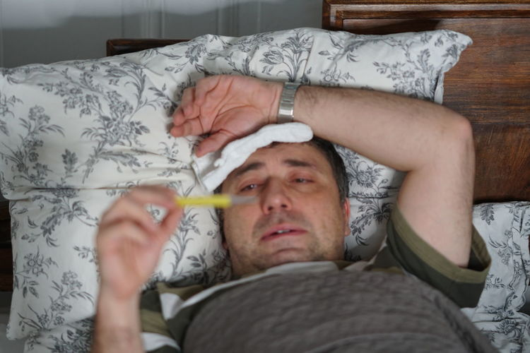 Man Checking Temperature While Lying On Bed At Home
