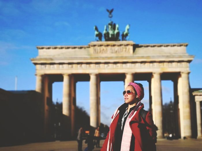 Woman standing against brandenburg gate