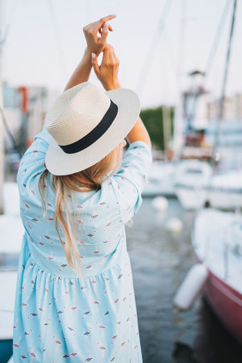 Beautiful blonde young woman in blue dress and straw hat from back at pier in the sunset time