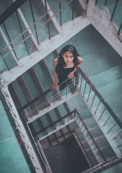 High angle portrait of smiling woman standing on staircase