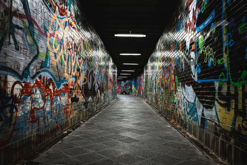 Graffiti on wall in illuminated tunnel