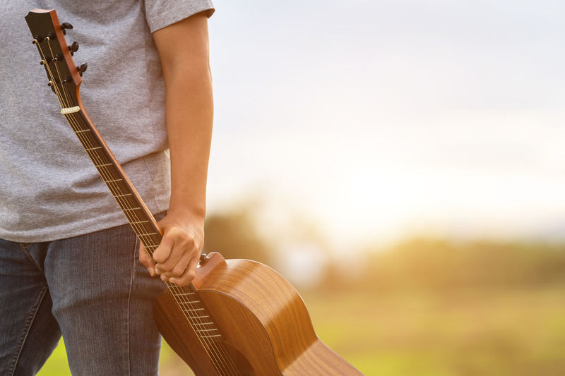 Midsection of man holding guitar against sky