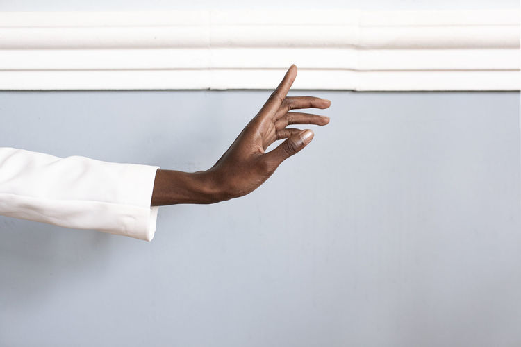 Cropped hand of person gesturing by wall