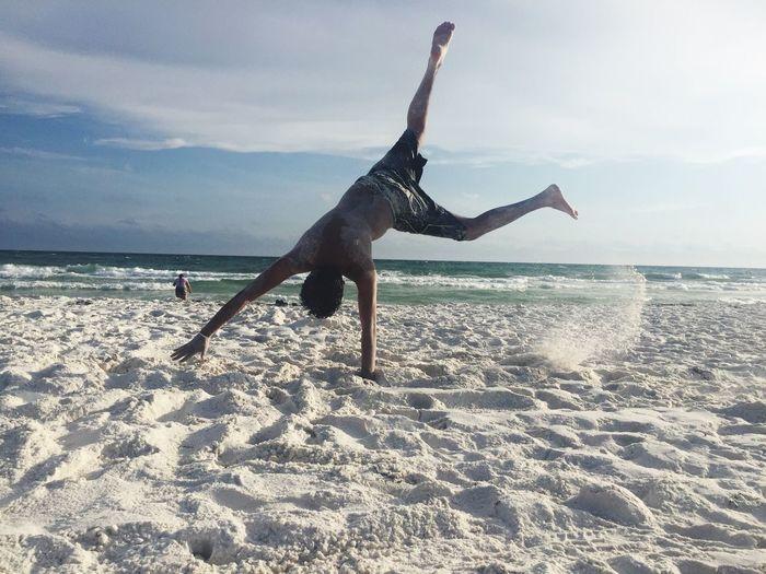 Full Length Of Man Doing Cartwheel At Beach Against Sky