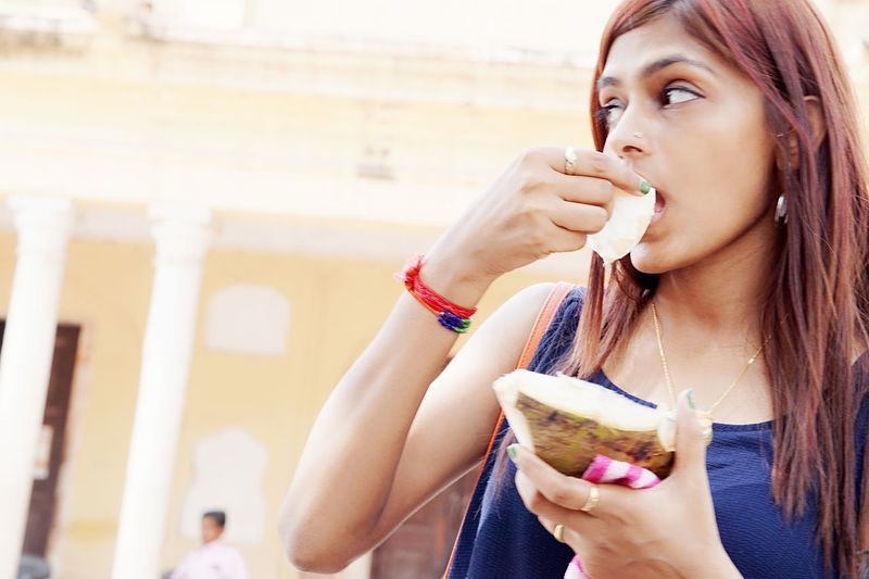 Low angle view of young woman eating coconut while standing on street