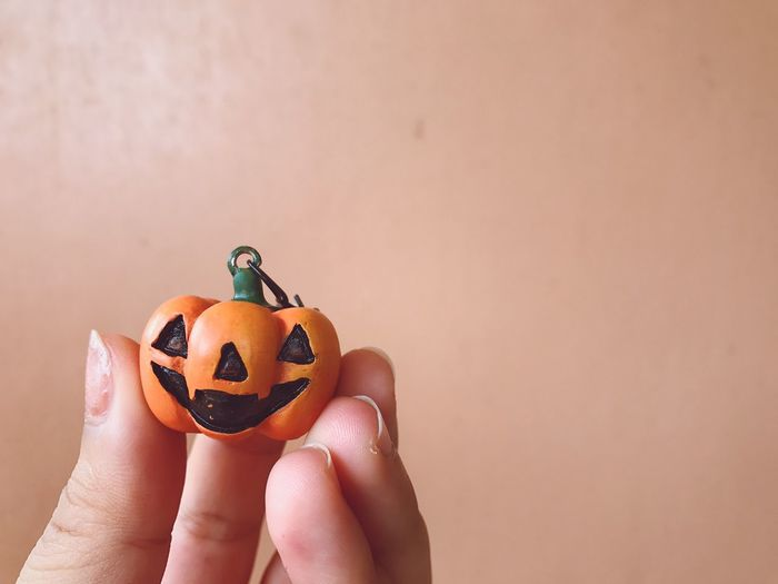 Close-Up Of Human Hand Holding Jack O Lantern Pendant During Halloween