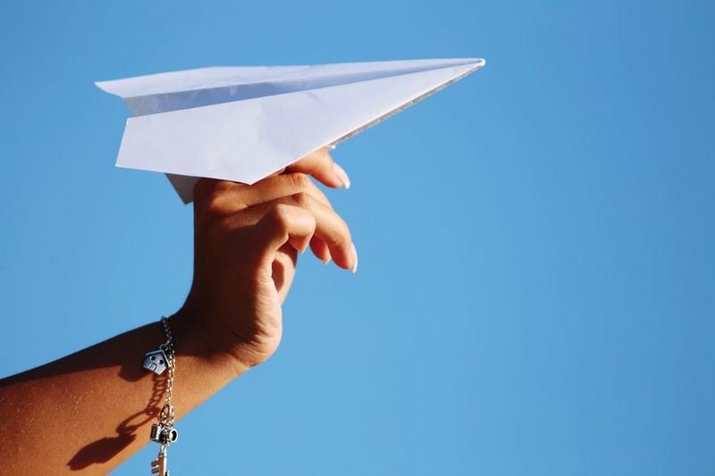 Cropped hand of woman holding paper airplane against clear blue sky