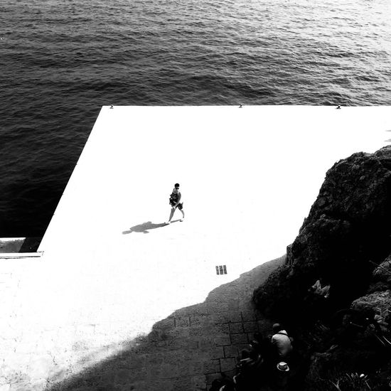 High angle view of people on rock by sea