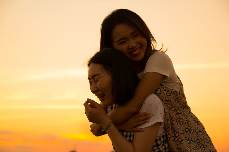 Woman Piggybacking Friend Against Sky During Sunset