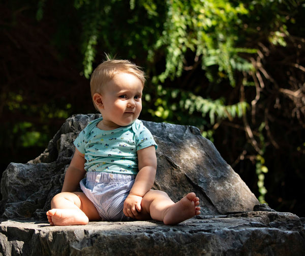 Cute Boy Looking Away While Sitting On Rock