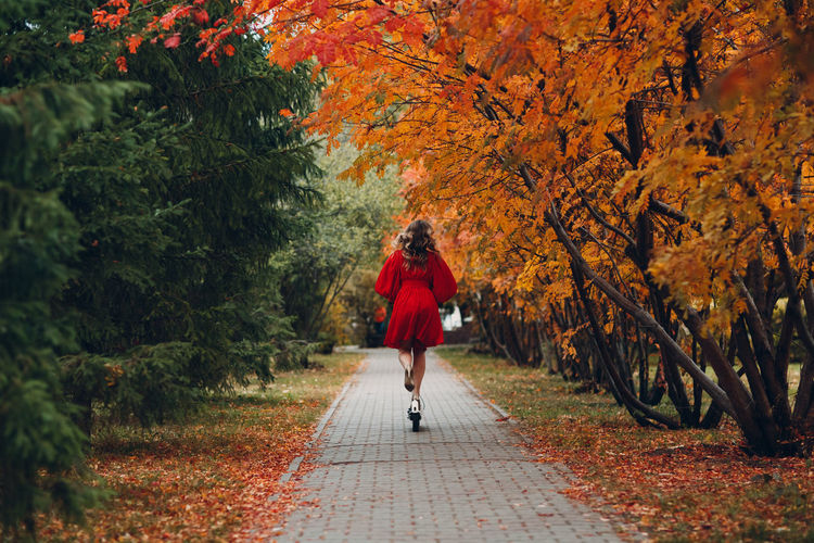 Woman walking on footpath during autumn