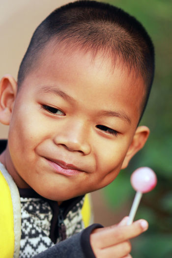 one boy be smile when eat candy ASIA Smile Gread Happy Mood Candy Portrait Child Childhood Headshot Looking At Camera Holding Close-up Pretty Formal Portrait