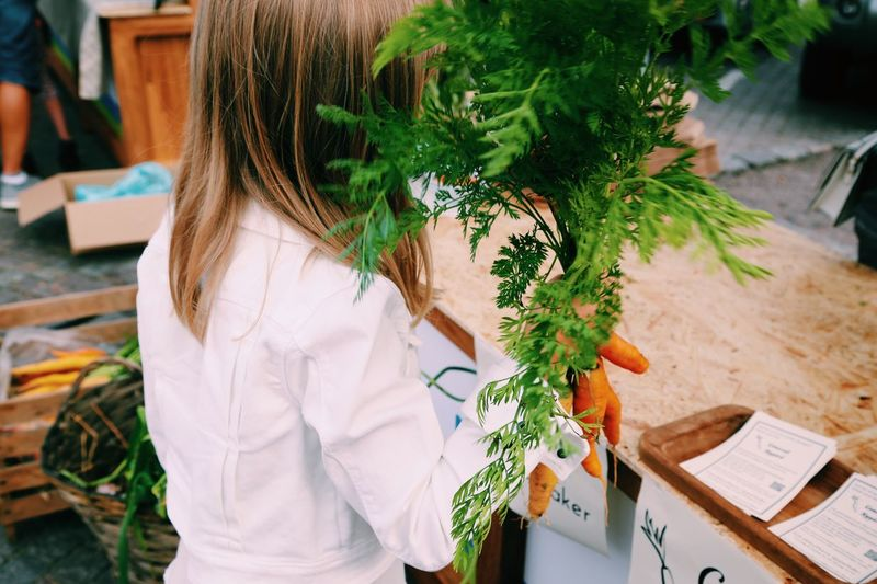 Rear View Of Girl Selling Fresh Carrots At Farmer Market