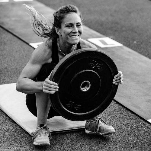 Athlete Lifting Weights While Crouching Outdoors