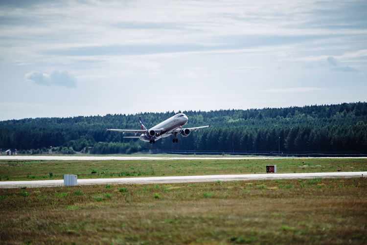 Airplane flying over runway against sky